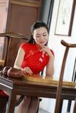 Китайская модель cheongsam сидит на игре табуретки идет Стоковая Фотография RF