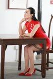 Китайская модель cheongsam сидит на табуретке Стоковое фото RF