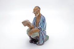 Китайская статуя книги чтения старика на белой предпосылке Стоковая Фотография