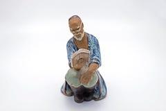 Китайская статуя книги чтения старика на белой предпосылке Стоковое Изображение RF