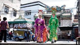 Китайские актеры оперы идя через улицу к предлагая святыне Чёрного моря Стоковые Изображения