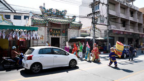 Китайские актеры оперы идя через улицу к предлагая святыне Чёрного моря Стоковые Фото