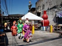 Китайские актеры оперы идя через улицу к предлагая святыне Чёрного моря Стоковые Фотографии RF