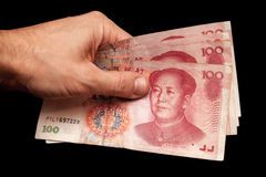 Китайские банкноты в мужской руке изолированной на черноте Стоковое Фото