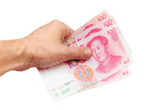 Китайские банкноты renminbi юаней в изолированной руке Стоковое Фото