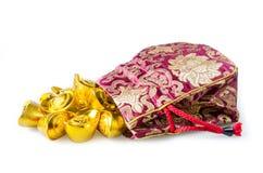Китайские золотые инготы при красный мешок изолированный на белой предпосылке Стоковые Фото