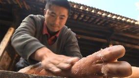 Китайские люди распространяют соль равномерно на ветчине и отжимают ее повторно к делать ветчину Nuodeng yunnan Китай стоковые фотографии rf