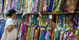 Китайские магазины женщины для рулонов ткани на стойле рынка стоковые фотографии rf
