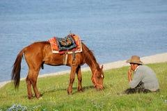 Китайские пастухи казаха с лошадью на озере Sailimu Стоковые Изображения RF