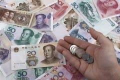 Китайские примечания и монетки денег (RMB) владение домашнего ключа принципиальной схемы дела золотистое достигая небо к Стоковые Изображения RF