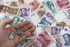 Китайские примечания и монетки денег (RMB) владение домашнего ключа принципиальной схемы дела золотистое достигая небо к Стоковая Фотография