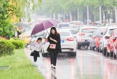 Китайские родители которые выбирают вверх их детей после школы Стоковые Изображения
