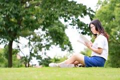 Китайские стекла носки девушки читая книгу на траве Стоковые Изображения RF