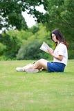 Китайские стекла носки девушки читая книгу на траве Стоковое фото RF