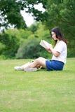 Китайские стекла носки девушки читая книгу на траве Стоковая Фотография RF