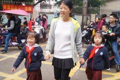 Китайские студенты в полдень по дороге домой от школы стоковые фото