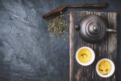 Китайские чайник и шар с зеленым чаем на каменном взгляд сверху предпосылки Стоковая Фотография RF