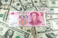Китайские юани CNY на предпосылке много долларов Стоковая Фотография RF