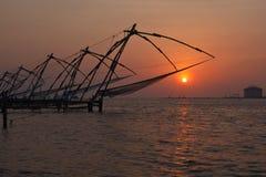 Китайские fishnets на заходе солнца. Kochi, Керала, Индия стоковая фотография