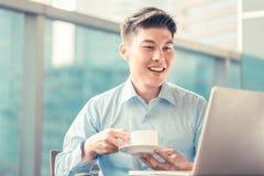 Китайский бизнесмен имея кофе на его компьтер-книжке сидя в фронте Стоковая Фотография RF