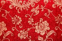 Китайский глянцеватый орнамент на красной ткани Стоковое Изображение RF