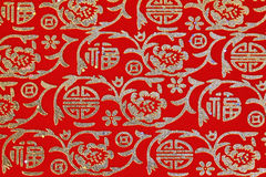 Китайский глянцеватый орнамент на красной ткани Стоковое Фото