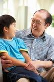 Китайский дед и внук ослабляя дома стоковые фотографии rf