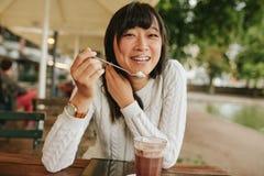 Китайский женский наслаждаясь десерт на кафе Стоковые Изображения