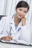 Китайский женский доктор больницы сочинительство женщины в офисе Стоковая Фотография RF