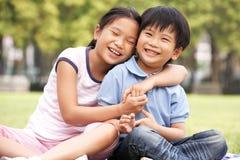 Китайский мальчик и девушка сидя в парке совместно Стоковая Фотография