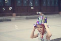Китайский мальчик играя soapbubbles Стоковые Изображения RF