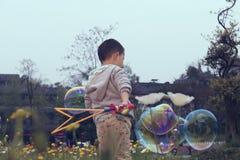 Китайский мальчик играя soapbubbles Стоковое фото RF