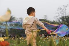 Китайский мальчик играя soapbubbles Стоковые Фото