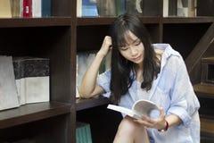 Китайский портрет молодой красивой женщины читает книгу в Bookstore Стоковая Фотография