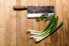 Китайский прерывая нож с зелеными луками на деревянной разделочной доске стоковые фотографии rf