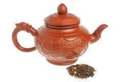Китайский чайник глины, изолированная пригорошня зеленого чая Стоковая Фотография
