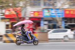 Китайский человек на электрическом самокате, Yiwu, Китай Стоковое Изображение