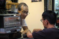 Китайский человек ремонтируя электроприборы в Гонконге Стоковое Фото