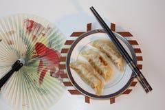 3 китайских вареника сидят на плите с палочками и красным вентилятором Стоковое Изображение RF
