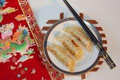 3 китайских вареника сидят на плите с палочками и красным переченем Стоковая Фотография RF