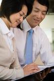 2 китайских предпринимателя читая документ Стоковые Изображения