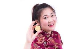 Китайцы красивой молодой азиатской женщины нося одевают традиционное cheongsam или qipao при рука держа золотое Bitcoin изолирова стоковые фото