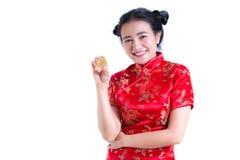 Китайцы красивой молодой азиатской женщины нося одевают традиционное cheongsam или qipao при рука держа золотое Bitcoin изолирова стоковая фотография