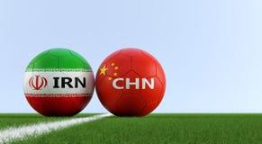 Китай против Футбольный матч Ирана - футбольные мячи в цветах Китаев и Irans национальных на футбольном поле Стоковые Фотографии RF