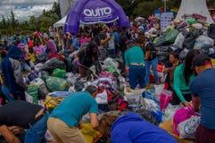 Кито, эквадор - 17-ое апреля 2016: Толпа людей Кито обеспечивая еду, одежды, медицину и воду гуманитарной помощи Стоковое Изображение RF