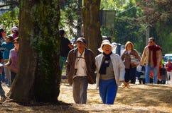 КИТО, ЭКВАДОР - 7-ОЕ ИЮЛЯ 2015: 2 взрослого с предохранением от солнца идя через парк для того чтобы приехать к Папе Франсиско ск Стоковая Фотография RF