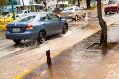 КИТО, ЭКВАДОР - 20-ОЕ СЕНТЯБРЯ 2016: Автомобиль едет на затопленной дороге в городе Кито после проливного дождя Стоковая Фотография