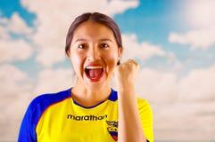 КИТО, ЭКВАДОР -8 ОКТЯБРЬ 2016: Молодая эквадорская женщина нося камеру облицовки официальной рубашки футбола марафона стоящую Стоковая Фотография RF