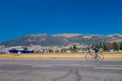 КИТО, ЭКВАДОР - MARZO 23, 2015: На дороге неопознанная тренировка велосипедиста и большой взгляд за им, солнечный день Стоковые Изображения RF