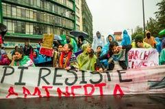 Кито, эквадор - 27-ое августа 2015: Группа в составе сердитое смешанное молодые люди задерживая знамя и протестуя сердито в город Стоковое Фото